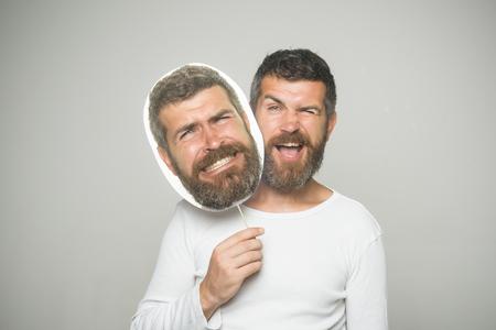Man of bebaarde man op grijze achtergrond. Gevoel en emoties. Man met lange baard en snor. Hipster met knipogen en eng gezicht houdt portret naamplaatje. Kapper mode en schoonheid. Stockfoto