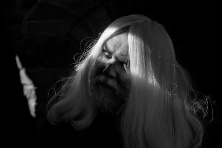 Druid old man face with wrinkles long silver beard and hair with bright light on dark background Stock fotó