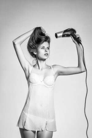 young woman with slim sexy body pretty face and brunette long hair in underwear holding hairdryer standing in studio on grey background
