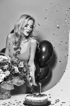 Pretty emotional young flirtatious blonde girl with long curly hair standing with birthday cake with candle near bunch of red balloons and flower bouquet in studio on yellow backdrop, vertical photo