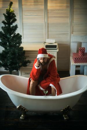 Home alone, bad santa in bath. Winter holiday and xmas party. Christmas man with beard, waiting. Hipster santa at Christmas tree drink wine, loneliness. Expectation, love and betrayal.
