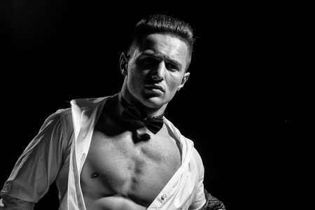 young handsome gentleman undressing fashion white shirt and bow tie in studio Фото со стока
