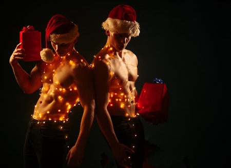 Christmas party and sex games. Twins santa with muscular body in garland. Young men in santa costume, present for girls. Call boys or sexy athlete men at xmas. New year strip and gifts for adults.