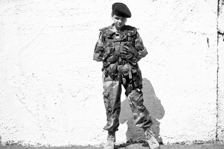 Little girl soldier with strict serious face in camouflage and black beret on her head standing on white wall background with hands on back