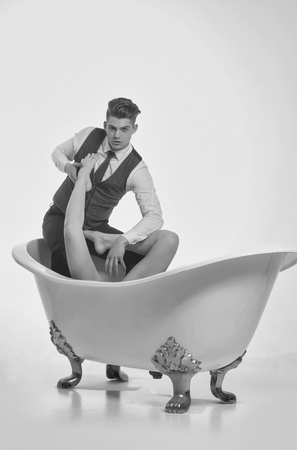 Handsome man or businessman with stylish haircut, hair, in fashion business wear, vest, shirt and pants relaxing with sexy, naked female legs, feet, in classic bath tub, isolated on white background Archivio Fotografico