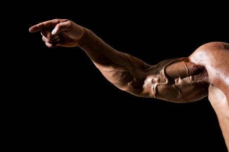 Main avec les veines, les muscles, les biceps, les triceps pointent du doigt sur fond noir. Force, concept de puissance. Sport, fitness, musculation. Banque d'images - 93025167