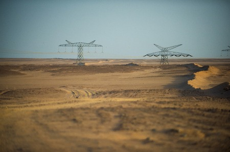 De lijntorens van de macht in woestijn op blauwe hemelachtergrond. Elektriciteitsdistributiestations. Elektrische energietransmissie. Opwarming van de aarde, klimaatverandering. Ecologie, ecomacht, technologieconcept.