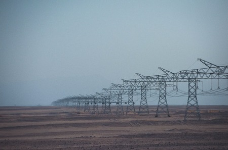 Electric energy transmission. Power line towers in desert on blue sky background. Ecology, eco power, technology concept. Electricity distribution stations. Global warming, climate change.