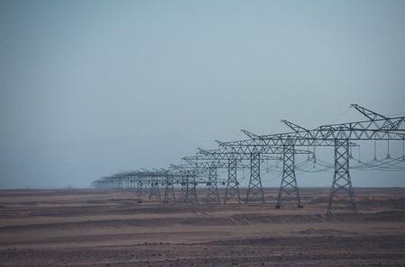Elektrische energietransmissie. De lijntorens van de macht in woestijn op blauwe hemelachtergrond. Ecologie, ecomacht, technologieconcept. Elektriciteitsdistributiestations. Opwarming van de aarde, klimaatverandering.