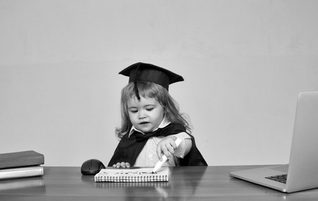 Cute boy small child in black squared hat and academic gown sitting at wooden school desk drawing by marker in exercise book near computer mouse notebook and diaries on gray background 写真素材 - 92579065