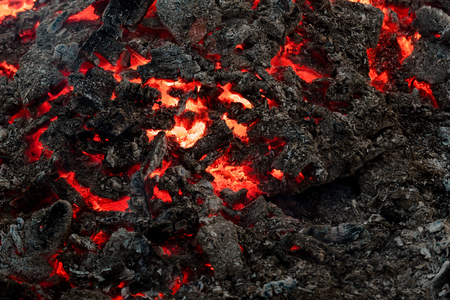 Lava flame on black ash background. Formation, geology, nature, environment. Danger, hazard, energy concept. Volcano, fire, crust. Magma textured molten rock surface.