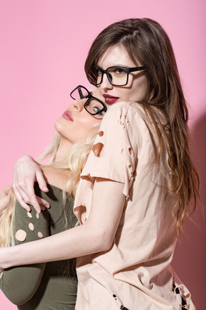 Women or girls in nerd glasses hug on pink background. Love, lgbt, relationship, romance, lesbian, lifestyle. Fashion, beauty, look concept