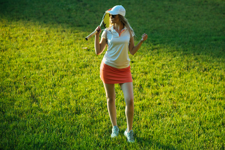 Girl athlete in sexy uniform, cap on green grass. Sport, game concept. Fashion, beauty, style. Woman player with tennis racket pose on lawn. Activity, energy, health.