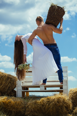 Woman with long hair in white dress with flowers. Couple in love hug on bench on blue sky. Summer vacation concept. Man with muscular torso hold wicker basket. Romance, relationship, relations.