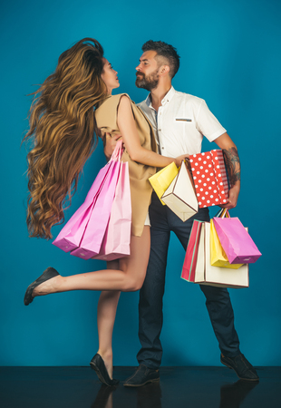 Girl and bearded man hold present pack, cyber Monday. Couple in love hold shopping bag near blue wall. Shopping and sale. Fashion shopaholic couple. Black Friday, happy holiday, relations.