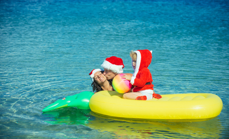 Santa child, parents at Christmas. Christmas happy family on pineapple mattress in water. New year man, girl with small boy. Xmas party celebration, fathers and mothers day. Winter holiday vacation.