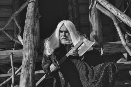 長い銀髪と長い銀髪のひげを持つ老人ドルイドは、木製の家の背景晴れた日の屋外に大きな鋭い斧を保持毛皮のコートで