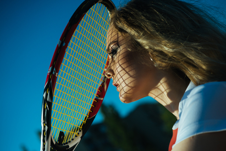 Beauty, look, skincare. Woman player with tennis racket on sunny day. Sport, game concept. Girl athlete with net shadow on face on sunny day. Activity, energy, health. Stock Photo