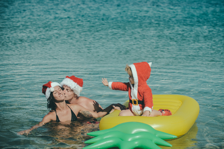 Santa child, parents at Christmas. Christmas happy family on pineapple mattress in water. Winter holiday vacation. Xmas party celebration, fathers and mothers day. New year man, girl with small boy.