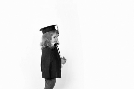 Little boy kid blond with smiling cute face in black academic squared cap and mantle holding wooden cube in hands standing ob white background isolated