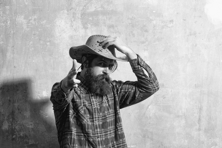 Bearded man, caucasian hipster, with long beard and moustache wearing cowboy hat and plaid shirt poses on beige grunge wall background