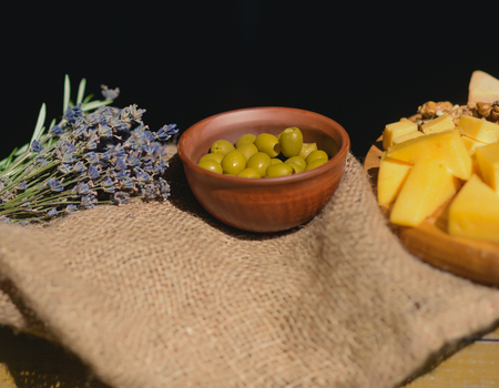 Olives in clay bowl, cheese plate and lavender bunch on sack cloth on black background. Still life on table. Food, appetizer, cuisine concept.