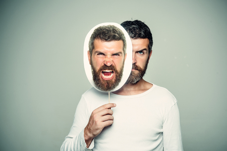灰色の背景に男やあごひげの男。深刻で怒っている顔を持つヒップスターは、肖像画のネームプレートを保持します。床屋のファッションと美しさ 写真素材