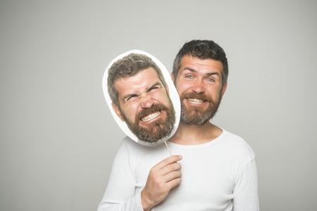 幸せで怒っている顔を持つヒップスターは、肖像画のネームプレートを保持します。感情と感情床屋のファッションと美しさ。長いあごひげと口ひ