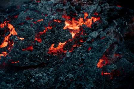 Volcano, fire, crust. Lava flame on black ash background. Formation, geology, nature, environment. Danger, hazard, energy concept. Magma textured molten rock surface. Archivio Fotografico