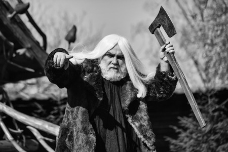 Brutal druid old man with long silver hair and beard in fur coat with axe in hand on blue sky background Stock Photo