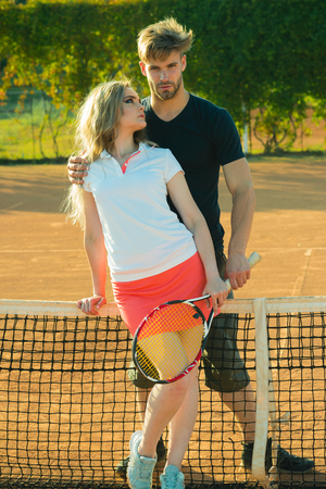 Couple in love stand at tennis net on clay court. Woman and man athletes hold tennis racket. Sport, game, match concept. Relationship, relations, family. Activity, energy, health.