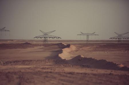 Elektriciteitsdistributiestations. De lijntorens van de macht in woestijn op grijze hemelachtergrond. Opwarming van de aarde, klimaatverandering. Elektrische energietransmissie. Ecologie, ecomacht, technologieconcept.