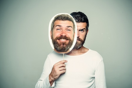 man met lange baard op ernstig en blij gezicht met papieren naamplaatje op grijze achtergrond Stockfoto