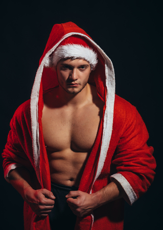 New year strip and gift for adult. santa with muscular body in red coat. Christmas party and sex games. Young man in santa costume, present for girls. Call boy or sexy athlete man at xmas. Imagens