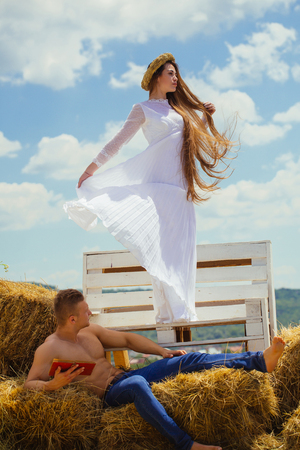 Woman with long hair in white dress stand on bench. Man read book on hay. Couple in love relax on cloudy blue sky. Romance, love, family. Summer vacation concept.