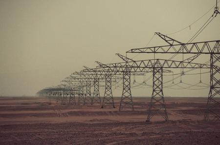 De lijntorens van de macht in woestijn op grijze hemelachtergrond. Opwarming van de aarde, klimaatverandering. Elektrische energietransmissie. Ecologie, ecomacht, technologieconcept. Elektriciteitsdistributiestations. Stockfoto