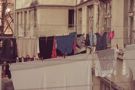 Clothes hang on clothesline at house backyard. Laundry, garment, linen dry on air outdoor. Ecology, eco, environment.