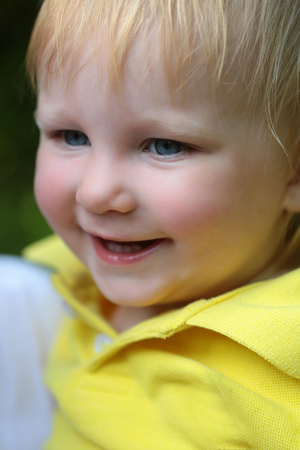 Kid boy smile with blue eyes on adorable face, blond hair on natural environment. Child, childhood, family. Happiness, innocence, infancy, future concept