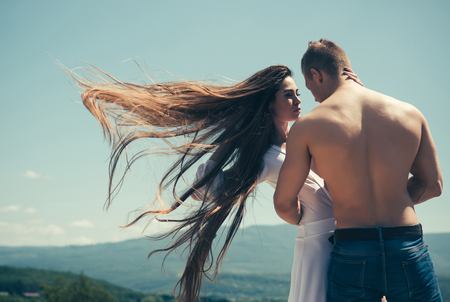 Summer vacation, wanderlust. Girl and macho with muscular torso on nature. Man hug woman with flying long hair on sunny day. Relationship, romance concept. Couple in love on blue sky.