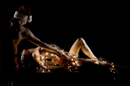 Jeux d'amour et de sexe. Père Noël et une fille avec un corps nu. Couple de Noël en amour d'homme et femme sexy. Relations du couple dans la guirlande lumineuse. Copain de nouvel an et petite amie isolée sur fond noir. Banque d'images - 92735903