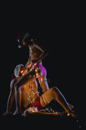 Love and sex games. Christmas couple in love of sexy man and woman. Santa man and girl with naked body. New year boyfriend and girlfriend isolated on black. Relations of couple in illuminated garland. Standard-Bild