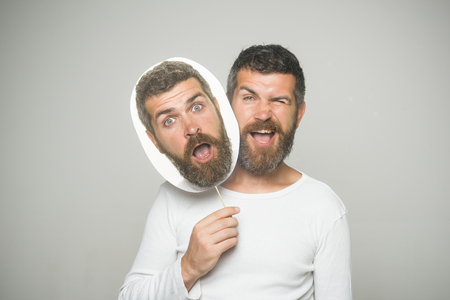 Man with long beard and mustache. Barber fashion and beauty. Feeling and emotions. Guy or bearded man on grey background. Hipster with winking and surprised face hold portrait nameplate.