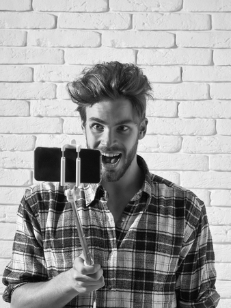 Excited handsome man young blond bearded male model with beard in plaid shirt uses smartphone or mobile phone on selfie stick on white brick background Banco de Imagens