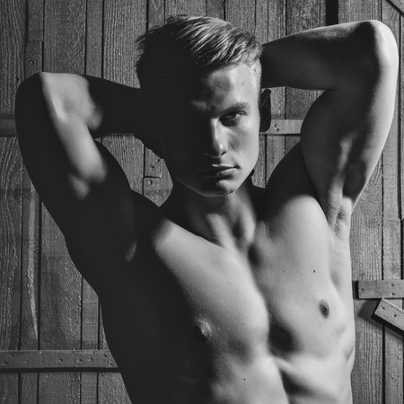 Young man with sexy body showing his muscular torso and abs in studio Zdjęcie Seryjne - 93075107