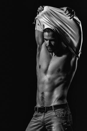 Knappe man of ongeschoren macho, bodybuilder, met stijlvol blond haar, kapsel, witte t-shirt uitkleden, toont sexy, gespierde torso, zes packs en abs, mannelijke striptease op zwarte achtergrond Stockfoto
