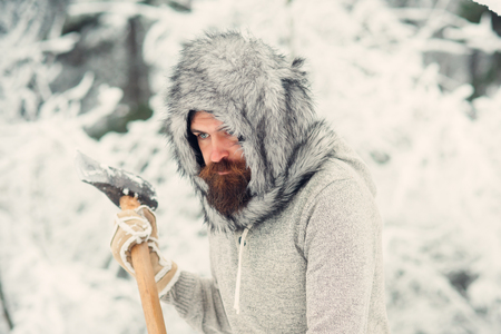 Camping, traveling and winter rest. Man lumberjack with ax. skincare and beard care in winter, beard warm in winter. Bearded man with axe in snowy forest. Temperature, freezing, cold snap, snowfall.
