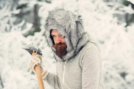 Camping, voyages et repos hivernal. Homme bûcheron avec une hache. soin de la peau et soin de la barbe en hiver, barbe chaude en hiver. Homme barbu avec une hache dans la forêt enneigée. Température, gelée, coup de froid, chute de neige.