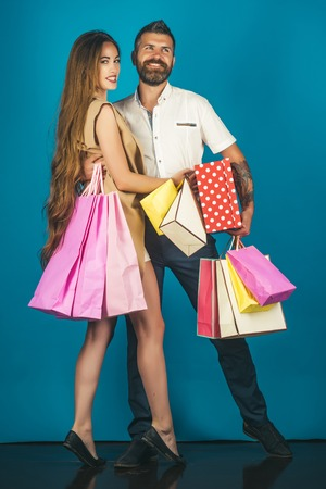 Shopping and sale. Girl and bearded man hold present pack, cyber Monday. Couple in love hold shopping bag near blue wall. Fashion shopaholic couple. Black Friday, happy holiday, relations.