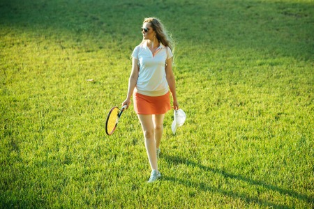 Girl athlete in sexy uniform with cap on green grass. Woman player with tennis racket walk on lawn. Sport, game concept. Fashion, beauty, style. Activity, energy, health. Stock Photo