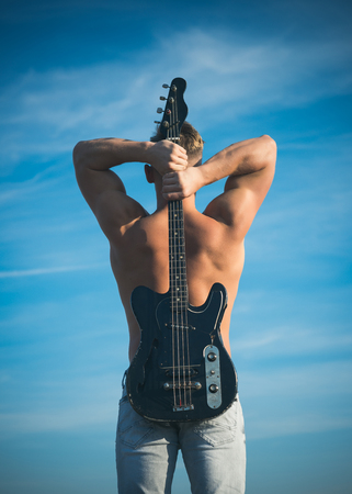 Sportsman with muscular back hold electric guitar on sunny blue sky. Music and sport concept